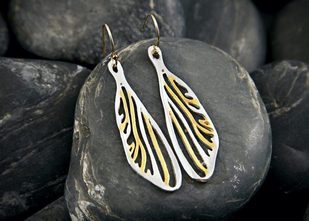 wing earrings on rocks